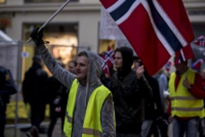 Morten Olsen i demonstrasjonen med norsk flagg og hansker med knokebeskyttelse. Foto: Researchkollektivet