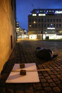 Parsayi sover utenfor Oslo domkirke. Nonen venner har lagt mursteiner på plakaten hans så den ikke skal blåse bort.